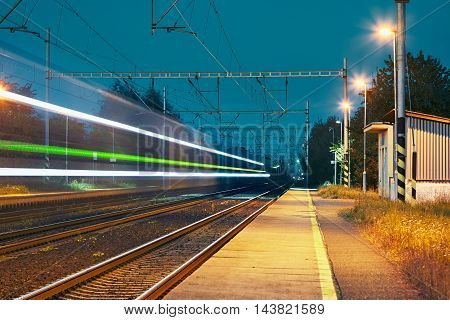 Railway station at the night. Passenger train on railroad tracks in blurred motion.
