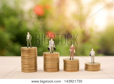 Business miniature people and money stack gold coin with business investment saving finance and banking concept.