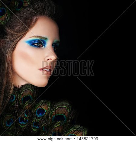 Glamorous Woman with Makeup and Peacock Feathers on Black Background
