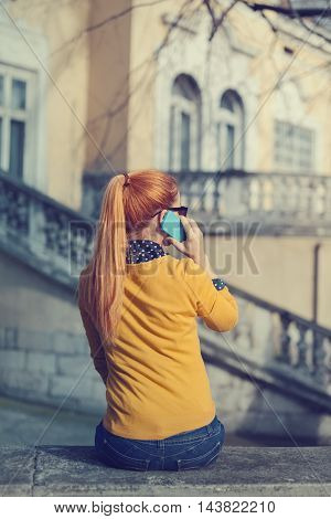 Young woman from the back talking on a smartphone
