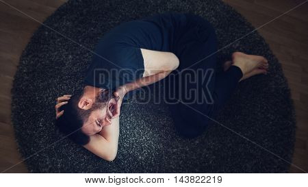 Young man in pain lying on the floor