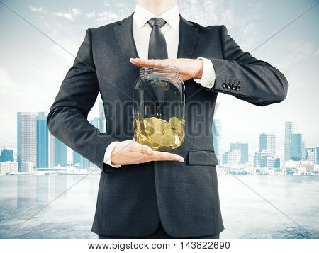 Businessman in suit holding glass jar with golden coins on abstract city background. Savings concept