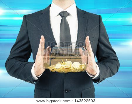 Businessman in suit holding glass jar with golden coins on abstract blue background. Savings concept