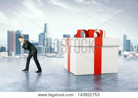 Businessman dragging huge present box on blurry city background. 3D Rendering