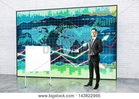 Handsome young fund manage giving presentation with blank flipboard and forex chart on white brick wall background. Mock up