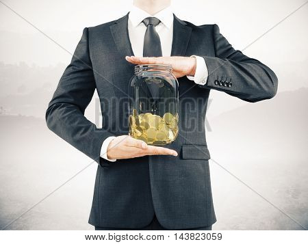 Businessman in suit holding glass jar with golden coins on abstract grey background. Savings concept