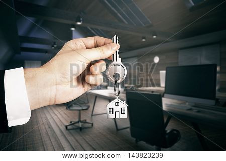 Realtor hand holding key with house keychain on office interior background. Real estate and mortgage concept