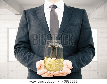 Businessman in suit holding glass jar with golden coins on interior background. Savings concept