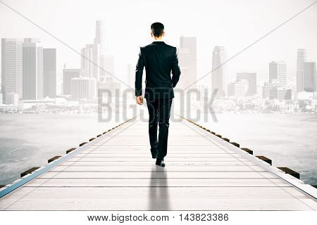 Businessman walking on wooden pier. Abstract city background. Success concept