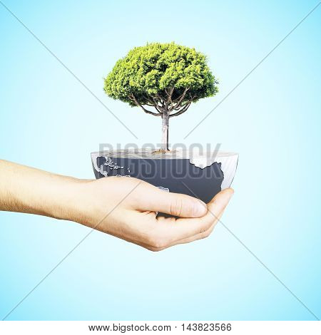 Male hand holding half a globe with large tree on blue background. Green earth concept. 3D Rendering