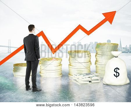 Financial growth concept with businessman looking at abstract golden coin ladder with upward arrow cash stack and bag on city background