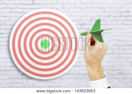 Targeting concept with businessman hand playing darts on white brick background. 3D Rendering