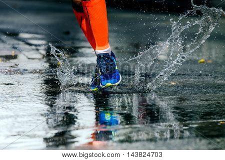 legs men in marathon compression socks running through a puddle water sprays