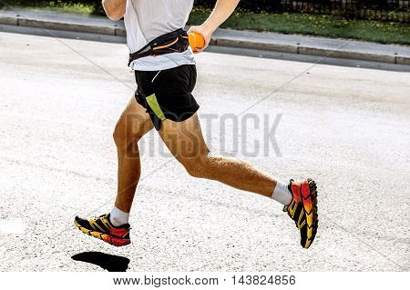 side view of foot men athlete runs through the streets of the city marathon