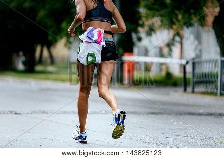 rear view wet water girl running marathon on city street