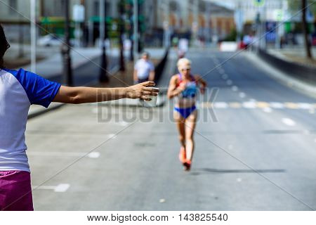 girl volunteer at hand сup with water in waterpoint of marathon in background running athlete