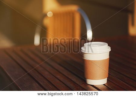 Paper cup of takeaway coffee on the wooden table in cafe. Place for your text or logo.