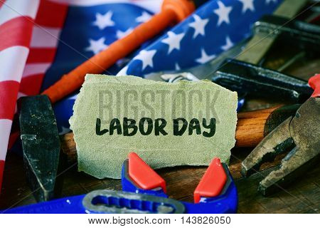 closeup of a piece of sandpaper with the text labor day written in it, a pile of different tools and a flag of the United States in the background