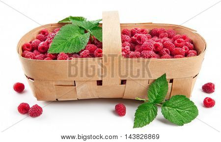 Fresh berries raspberry in wicker basket with green leaves. Isolated on white background