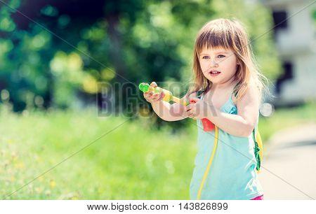 joyful little girl shooting with water pistol outside