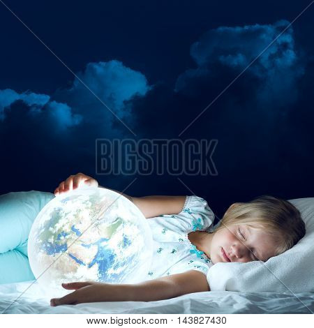 Cute girl in bed and looking at Earth planet. Elements of this image are furnished by NASA