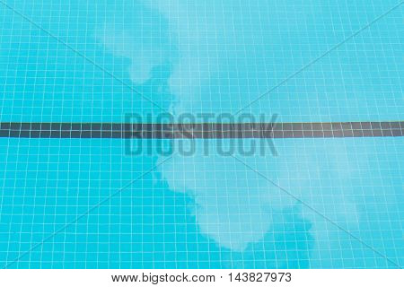 Blue swimming pool tile bottom and white cloud reflection in sunny day.