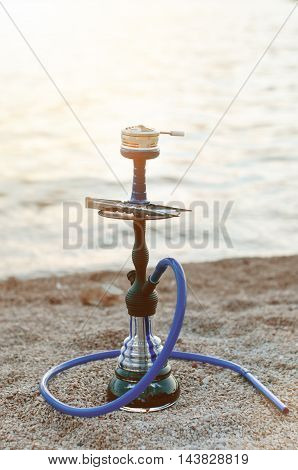 hookah and tabacoo. Smoking. Hookah on a beach. Sea like a background.