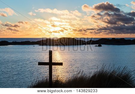 Black cross on a sand dune with a beach lake behind it at sunset.