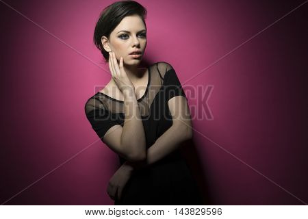 Beauty portrait of young pretty brunette girl wearing black elegant shirt isolated on pink background