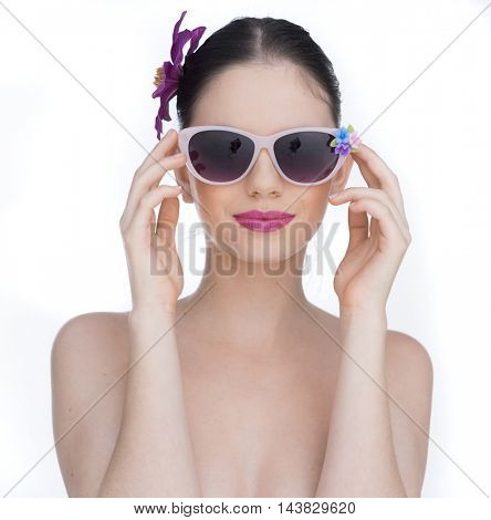 Beautiful face of a young and healthy girl with an orchid purple flower in her hair wearing sunglasses isolated on white background