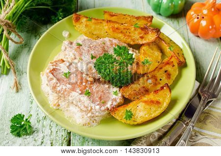 Pork chops with sour cream and baked potatoes. Rustic style