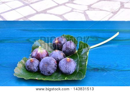 Sevenl ripe blue figs on big mulberry leaf on blue wooden table side view