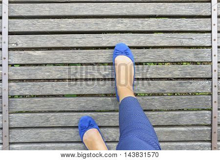 Feet in shoes on a wooden bridge. Close-up. View from above.