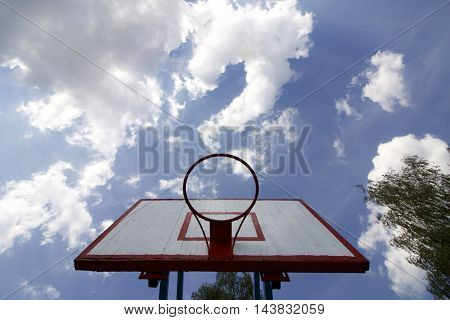 Basketball board without net. Old wooden planks. Painted. Located on a background of blue sky with clouds. Sport games in the yard. View from under the ring.