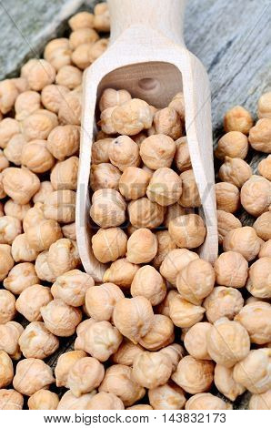Chickpeas in a wooden scoop on table