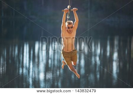 Man jumping into the water with a rope