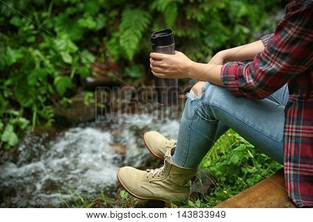 Girl relaxing with drink in forest