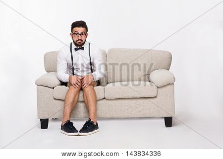 Picture of frightened or surprised handsome hipster man sitting on sofa or couch while posing isolated on white background in studio.