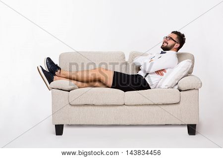 Picture of smiling handsome hipster man lying on couch or sofa and looking upwards. Young man lying with his arms crossed or folded isolated on white background.