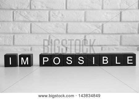 Black cubes with word IMPOSSIBLE on brick wall background