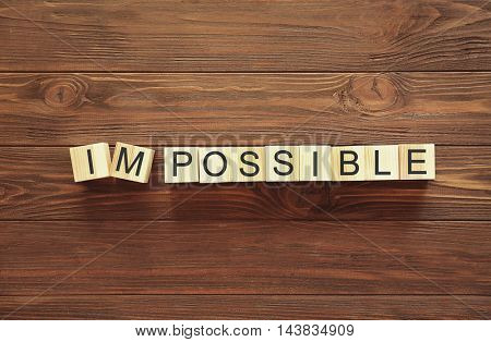 Cubes with word IMPOSSIBLE on wooden background