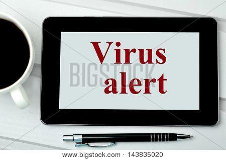 The words Virus alert on digital tablet pc