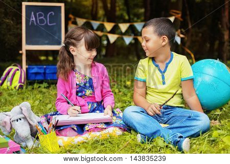 funny little children, a boy and a girl playing in the school. Back to school concept.