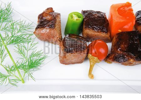 european food: grilled meat goulash on white plate with raw tomato, dill and olives