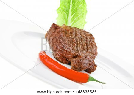 barbecued meat : beef ( lamb ) garnished with green lettuce and red chili hot pepper on white plate isolated over white background