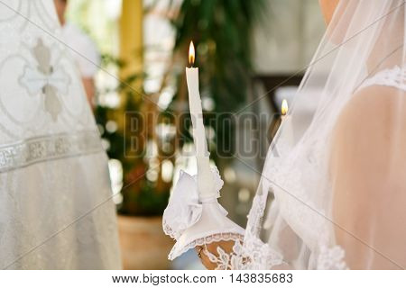 candle in hands of the bride at the wedding ceremony in the Orthodox Church. Soft focus selective focus