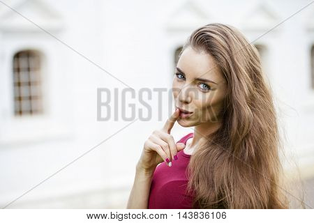 Young beautiful brunette woman has put forefinger to lips as sign of silence, outdoors