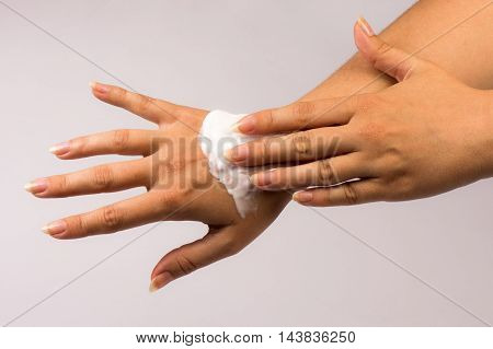Skincare with hand cream. Female hands on gray background.