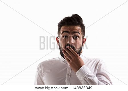 Portrait of shocked or surprised handsome man looking at camera in studio. Hipster man touching his beard isolated on white background.