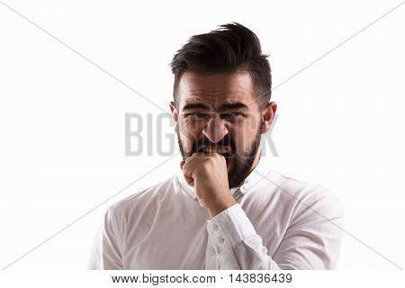 Studio shot. Emotions concept. Picture of shocked handsome man biting his wrist while posing for photographer isolated on white background.